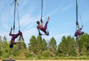 Three aerialists soar over the Open Space great lawn