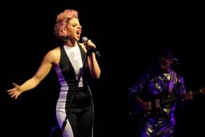 A performer holding her microphone and belting a high note.